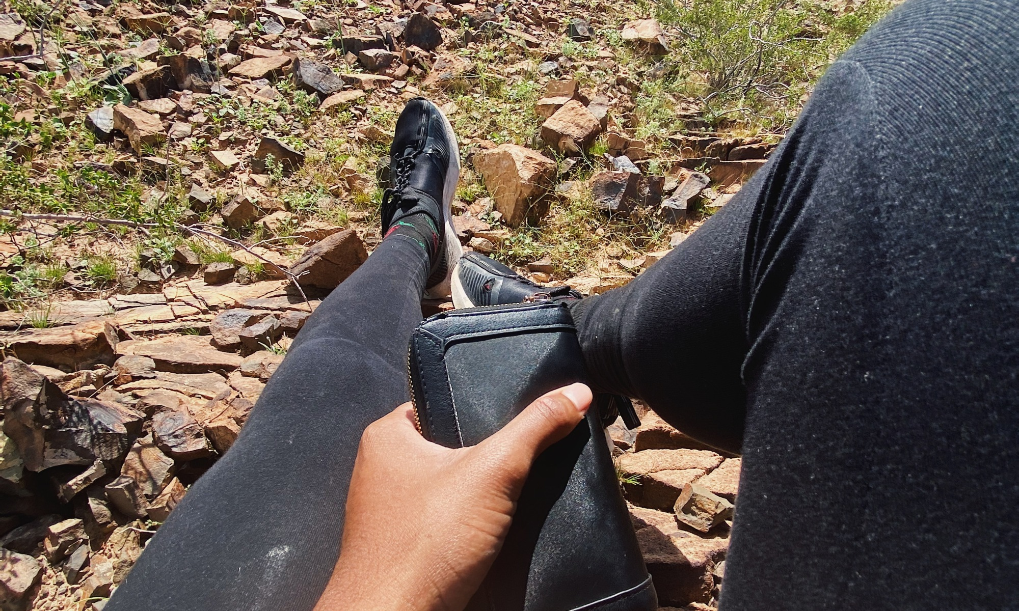 A pair of legs in black joggers overhangs a rocky desert landscape sprouted with sparse foliage.